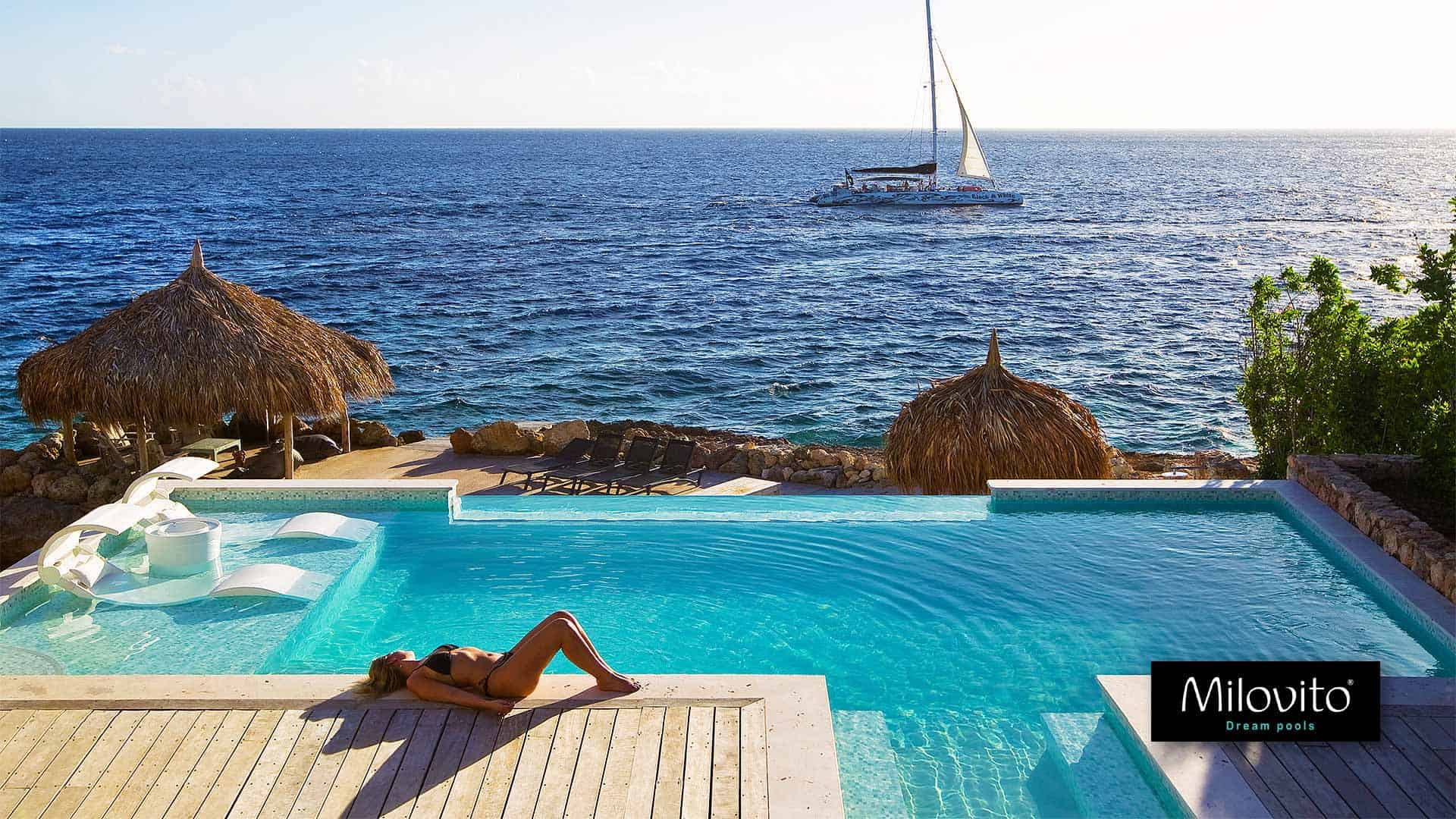 A bespoke swimming pool covered with light green glass mosaic at luxurious park Bocagentil, Curacao. Straight at the Caribbean Sea. Over the underwater window water falls to the second pool.